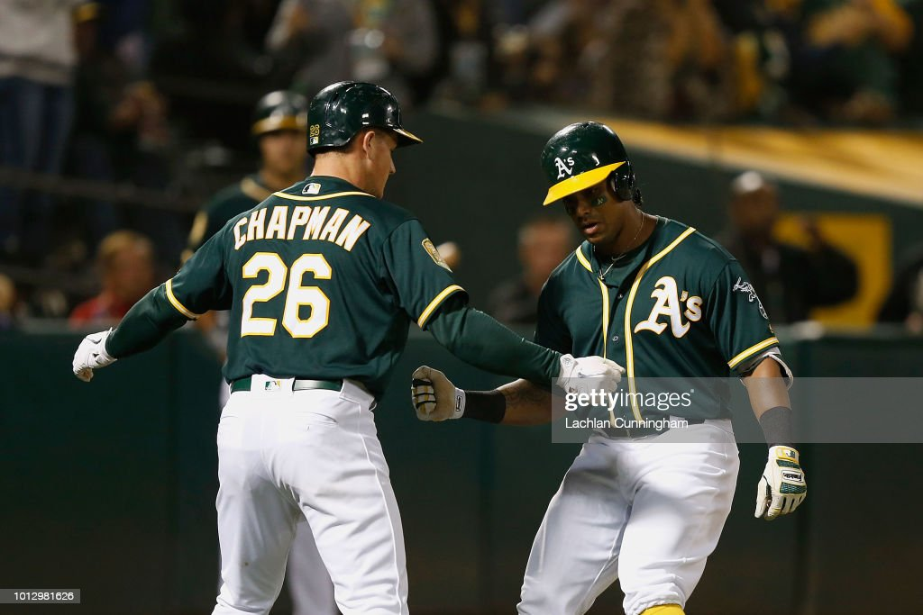 Khris Davis #2 of the Oakland Athletics celebrates with teammate Matt Chapman #26 after hitting a two-run home run in the sixth inning against the Los Angeles Dodgers at Oakland Alameda Coliseum on August 7, 2018 in Oakland, California.
