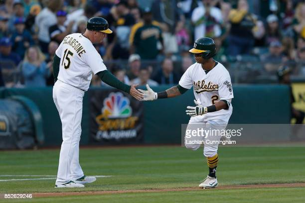 Khris Davis of the Oakland Athletics celebrates with third base coach Steve Scrasone after hitting a solo home run in the second inning against the...