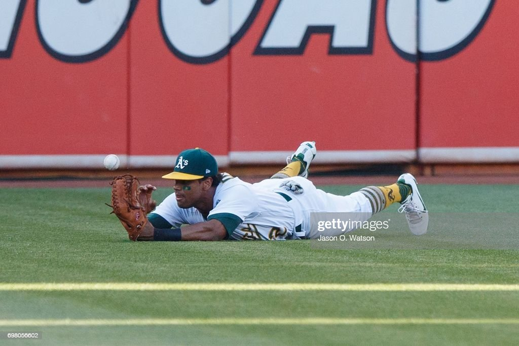 Khris Davis #2 of the Oakland Athletics dives for but is unable to catch a fly ball hit for a single by George Springer (not pictured) of the Houston Astros during the first inning at the Oakland Coliseum on June 19, 2017 in Oakland, California.