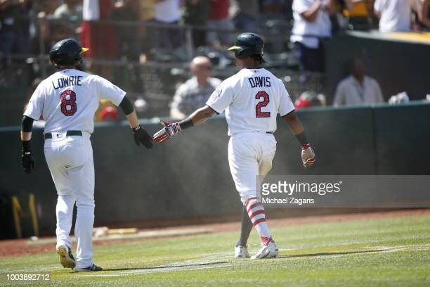 Khris Davis of the Oakland Athletics is congratulated by Jed Lowrie after scoring during the game against the San Diego Padres at the Oakland Alameda...