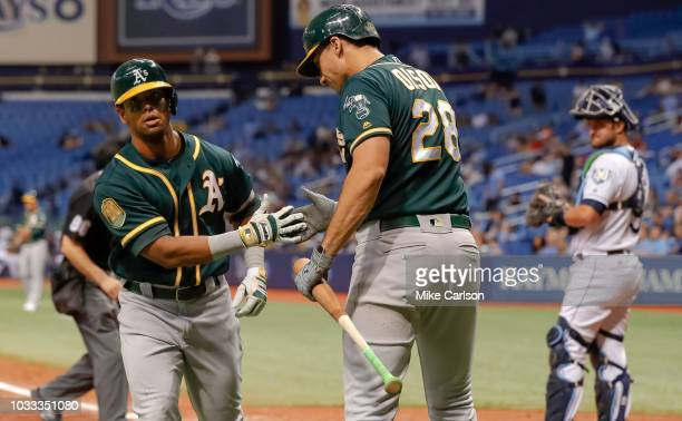 Khris Davis of the Oakland Athletics is congratulated by Matt Olson after his home run as Nick Ciuffo of the Tampa Bay Rays look on in the tenth...