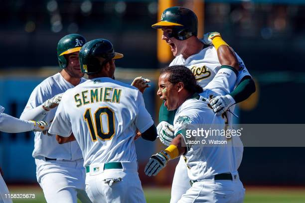 Khris Davis of the Oakland Athletics is congratulated by teammates after a walk off RBI during the ninth inning against the Texas Rangers at the...