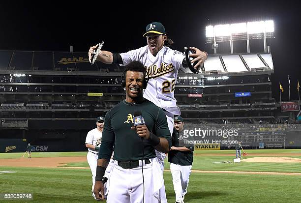 Khris Davis of the Oakland Athletics is hit with cream pies by Josh Reddick after Davis hit a walk off grand slam home run against the Texas Rangers...