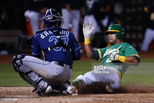 Khris Davis of the Oakland Athletics is tagged out at home by Travis d'Arnaud of the Tampa Bay Rays during the sixth inning at Oakland-Alameda County...