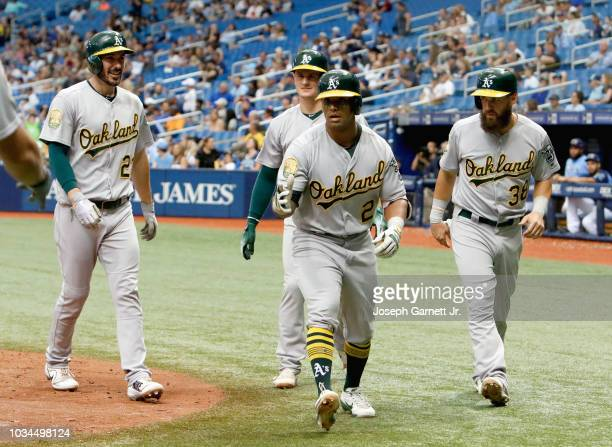 Khris Davis of the Oakland Athletics jogs off the field with teammates Matt Joyce Matt Chapman and Nick Martini after hitting a grand slam in the...