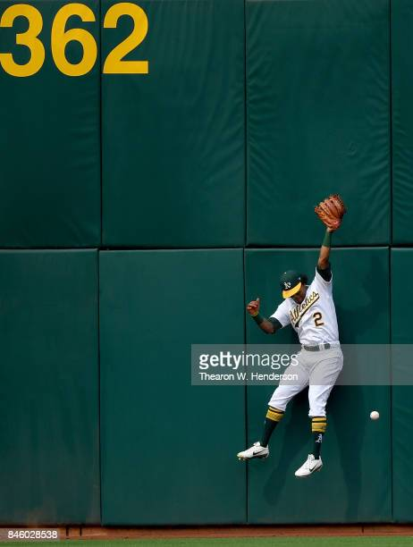 Khris Davis of the Oakland Athletics leaps at the wall for this ball that goes for a long single off the bat of Albert Pujols of the Los Angeles...