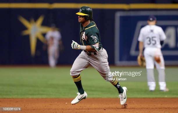 Khris Davis of the Oakland Athletics rounds the bases after his home run in the tenth inning of a baseball game against the Tampa Bay Rays at...