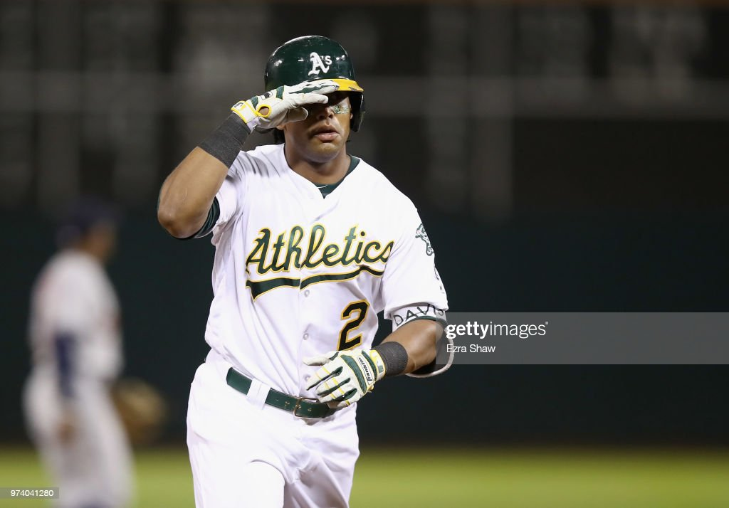 Khris Davis #2 of the Oakland Athletics salutes the dugout as he rounds the bases after hitting a home run in the eighth inning against the Houston Astros at Oakland Alameda Coliseum on June 13, 2018 in Oakland, California.