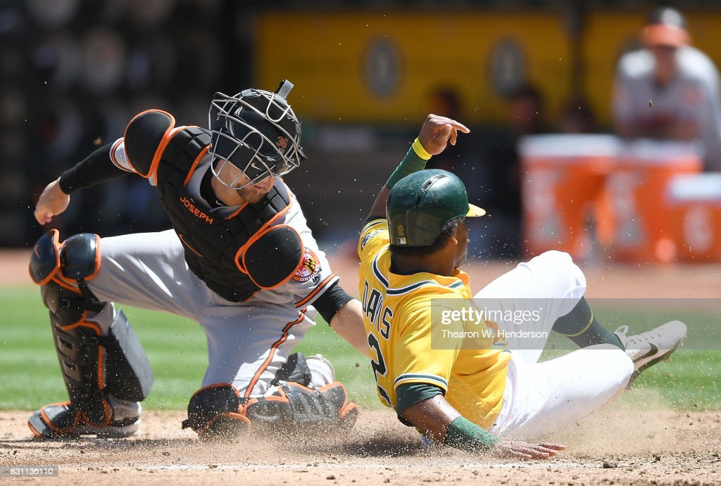 Khris Davis #2 of the Oakland Athletics scores sliding past the tag of Caleb Joseph #36 of the Baltimore Orioles in the bottom of the fourth inning at Oakland Alameda Coliseum on August 13, 2017 in Oakland, California.