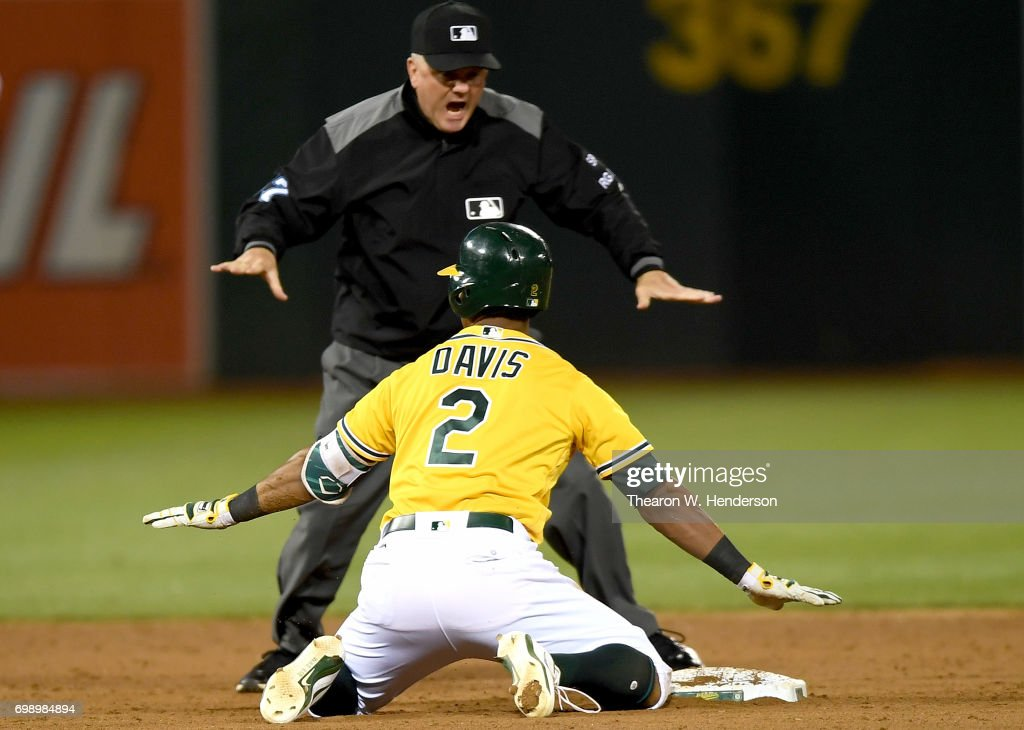 Khris Davis #2 of the Oakland Athletics signals safe with second base umpire Mike Everitt #57 after Davis dove into second with a double against the Houston Astros in the bottom of the six inning at Oakland Alameda Coliseum on June 20, 2017 in Oakland, California.