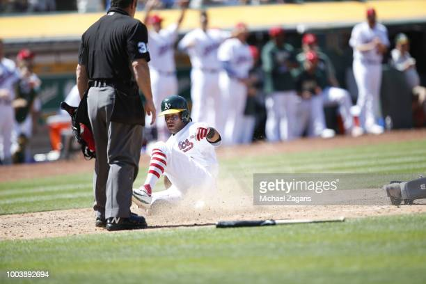 Khris Davis of the Oakland Athletics slides safely into home the bases during the game against the San Diego Padres at the Oakland Alameda Coliseum...