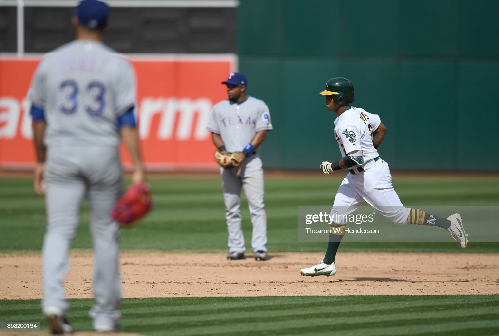 Khris Davis #2 of the Oakland Athletics trots around the bases after hitting a two-run homer off of Martin Perez #33 of the Texas Rangers in the bottom of the fifth inning at Oakland Alameda Coliseum on September 24, 2017 in Oakland, California.