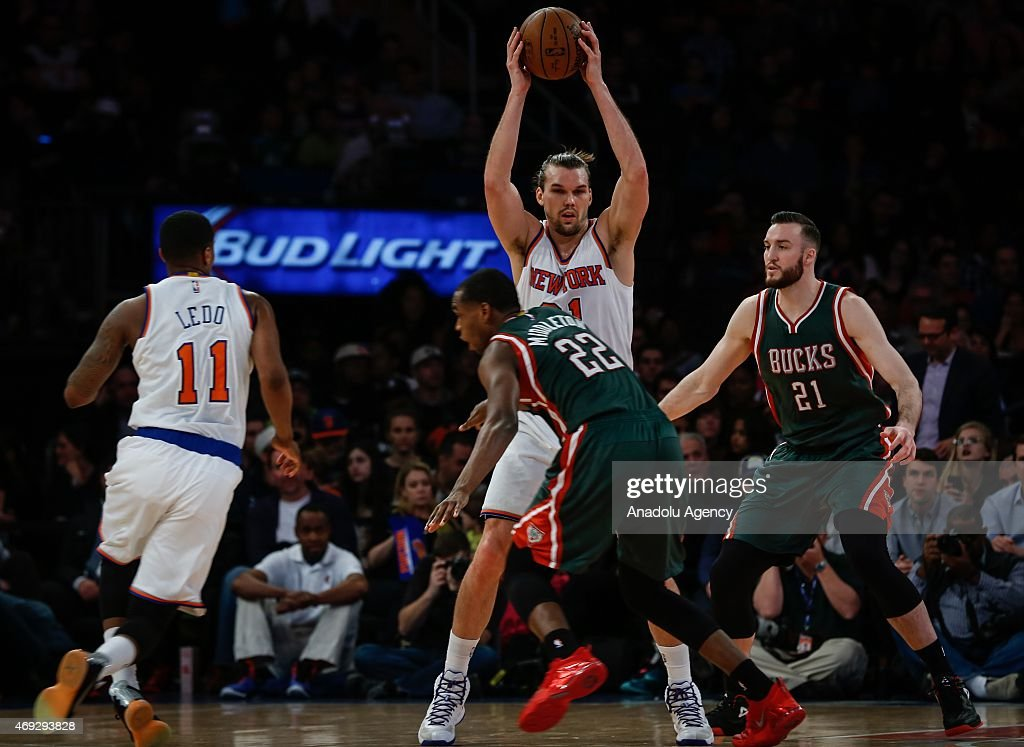 Khris Middleton #22 and Miles Plumlee #21 of the Milwaukee Bucks in action against Lou Amundson (C) and Ricardo Ledo #11 of the New York Knicks at Madison Square Garden on April 10, 2015 in New York, New York.