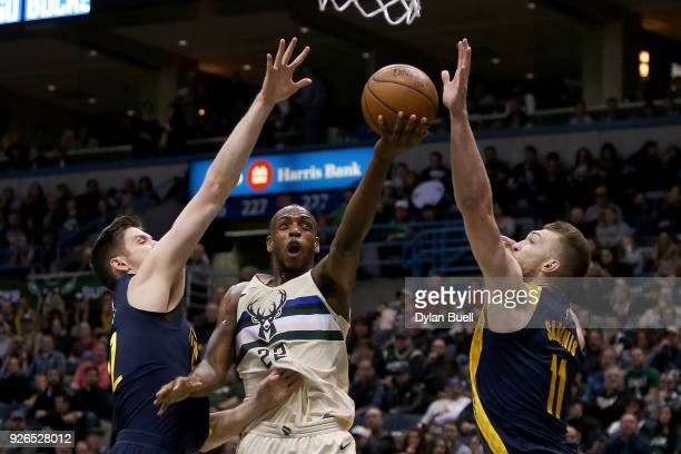 Khris Middleton of the Milwaukee Bucks attempts a shot between TJ Leaf and Domantas Sabonis of the Indiana Pacers in the first quarter at the Bradley...