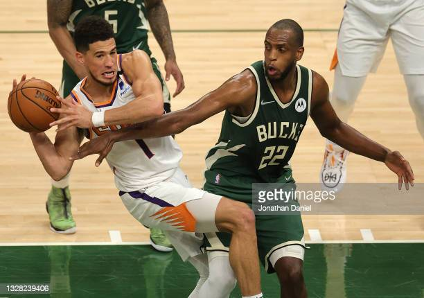 Khris Middleton of the Milwaukee Bucks attempts to steal the ball from Devin Booker of the Phoenix Suns as he looks to pass during the first half in...