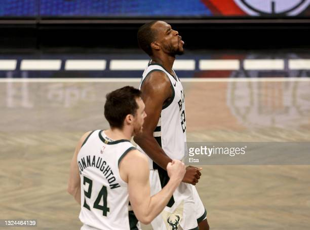 Khris Middleton of the Milwaukee Bucks celebrates after winning basket as teammate Pat Connaughton joins during the final minutes of overtime during...