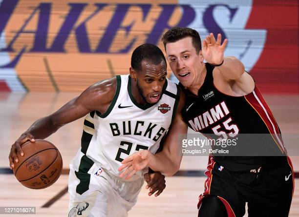 Khris Middleton of the Milwaukee Bucks drives the ball against Duncan Robinson of the Miami Heat during the fourth quarter in Game Four of the...
