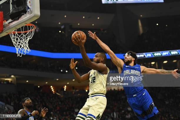 Khris Middleton of the Milwaukee Bucks drives to the basket against Michael CarterWilliams of the Orlando Magic during the first half of a game at...