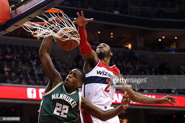 Khris Middleton of the Milwaukee Bucks dunks in front of John Wall of the Washington Wizards during the first half at Verizon Center on January 13...
