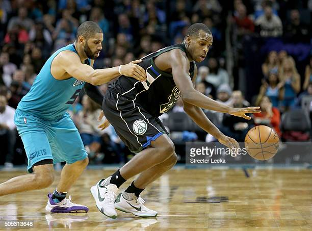 Khris Middleton of the Milwaukee Bucks goes after a looes ball against Nicolas Batum of the Charlotte Hornets during their game at Time Warner Cable...