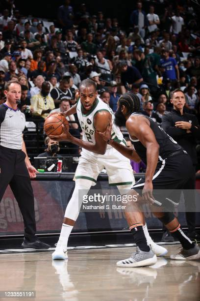 Khris Middleton of the Milwaukee Bucks handles the ball as James Harden of the Brooklyn Nets plays defense during the game during Round 2, Game 7 of...