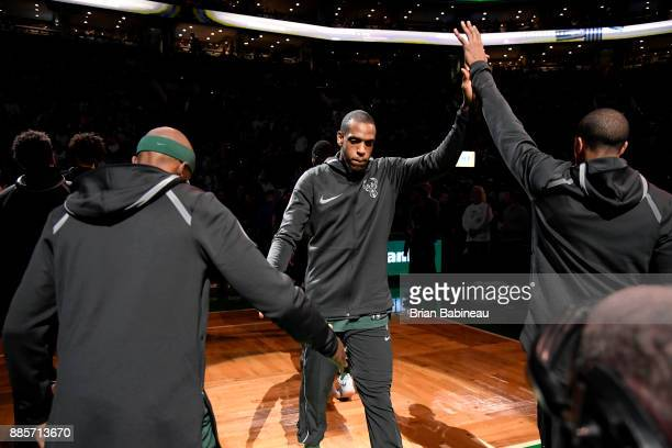 Khris Middleton of the Milwaukee Bucks high fives his teammates before the game against the Boston Celtics on December 4 2017 at the TD Garden in...