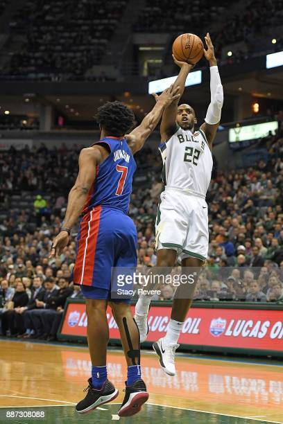 Khris Middleton of the Milwaukee Bucks is fouled by Stanley Johnson of the Detroit Pistons during the first half of a game at the Bradley Center on...