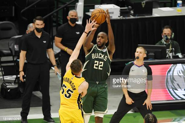 Khris Middleton of the Milwaukee Bucks makes a basket in overtime against Duncan Robinson of the Miami Heat during Game 1 of their Eastern Conference...