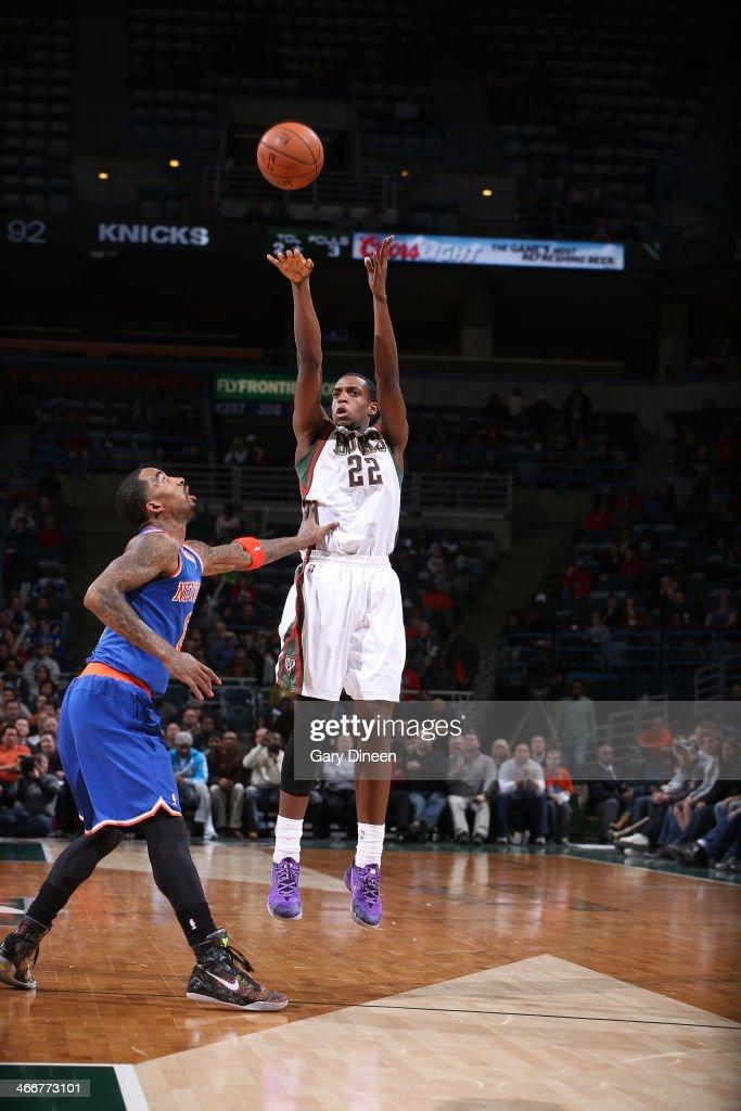 Khris Middleton #22 of the Milwaukee Bucks shoots against J.R. Smith #8 of the New York Knicks on February 3, 2014 at the BMO Harris Bradley Center in Milwaukee, Wisconsin.