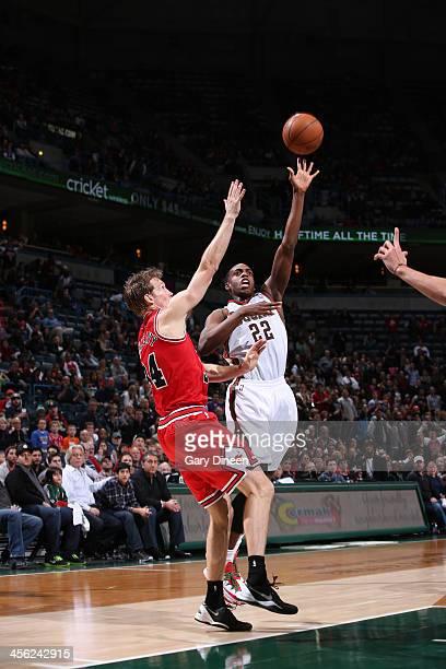 Khris Middleton of the Milwaukee Bucks shoots against Mike Dunleavy of the Chicago Bulls on December 13 2013 at the BMO Harris Bradley Center in...