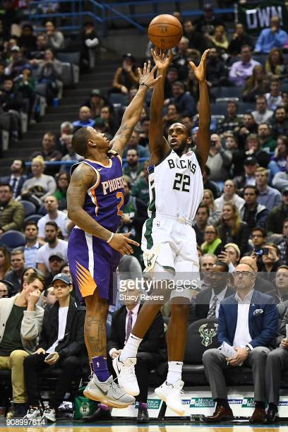 Khris Middleton of the Milwaukee Bucks shoots over Isaiah Canaan of the Phoenix Suns during the second half of a game at the Bradley Center on...