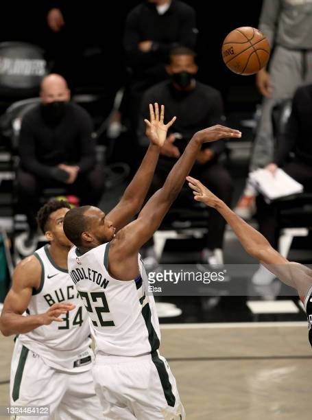 Khris Middleton of the Milwaukee Bucks shoots the game winning basket as teammate Giannis Antetokounmpo looks on in the final minutes of overtime...