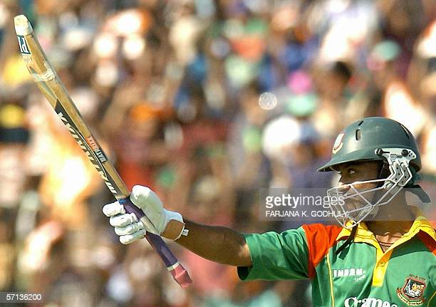 Bangladeshi batsman Aftab Ahmed raises his bat on reaching his half century during the second One Day International cricket match between Bangladesh...