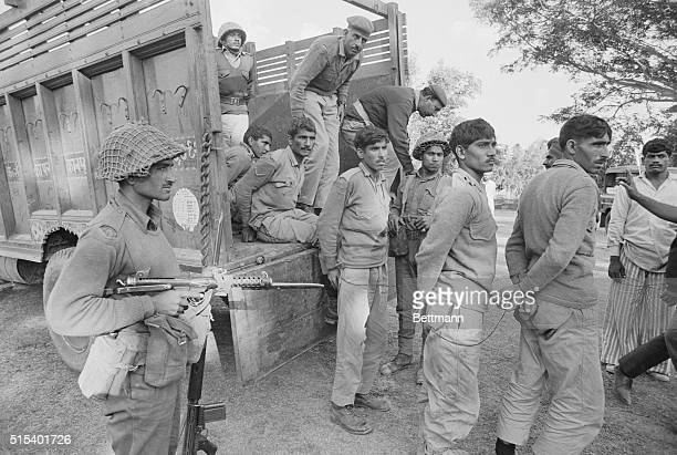 Armed Indian soldier supervises the unloading of Pakistani prisoners captured during battle at Khulna December 16 located about 90 miles northeast of...