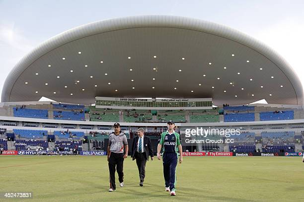 Khurram Khan captain of UAE walks out to toss the coin with match referee David Jukes and William Porterfield captain of Ireland ahead of the Ireland...