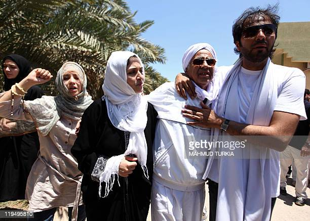 Khuwildi Hemidi a veteran comrade of Libyan leader Moamer Kadhafi walks with his son Khaled and other members of the family during the funeral of...
