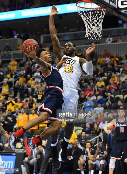 Khwan Fore of the Richmond Spiders drives to the hoop in front of Mo AlieCox of the Virginia Commonwealth Rams during the semifinals of the Atlantic...