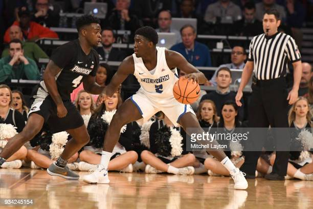 Khyri Thomas of the Creighton Bluejays posts up against Maliek White of the Providence Friars during the quarterfinal round the Big East Men's...
