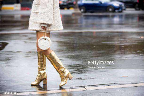 Ki Eunse, wearing a cream decorated jacket, Chanel bag and gold boots, is seen outside the Chanel show during Paris Fashion Week - Womenswear Spring...