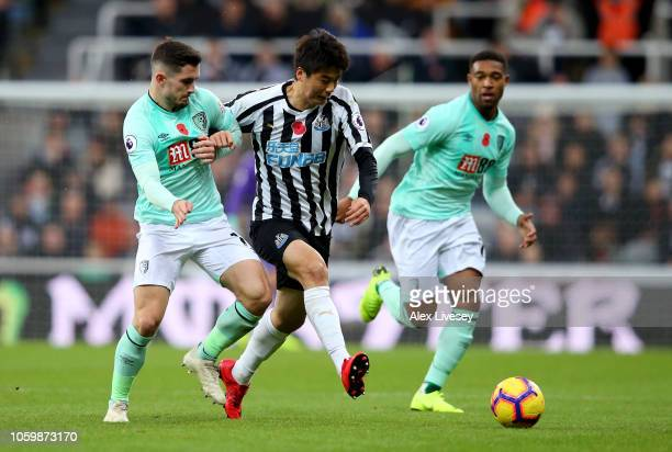 Ki SungYeung of Newcastle United battles for possession with Lewis Cook of AFC Bournemouth during the Premier League match between Newcastle United...