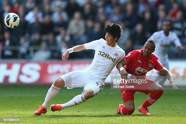 Ki Sung-Yeung of Swansea City locks arms with Nathaniel Clyne of Southampton during the Barclays Premier League match between Swansea City and...