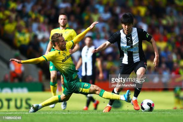 Ki SungYueng of Newcastle is tackled by Tom Trybull of Norwich during the Premier League match between Norwich City and Newcastle United at Carrow...
