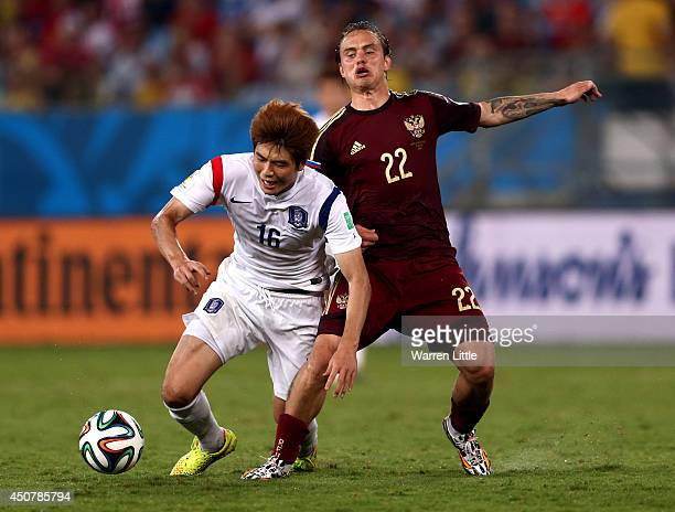 Ki SungYueng of South Korea and Andrey Yeshchenko of Russia battle for the ball during the 2014 FIFA World Cup Brazil Group H match between Russia...