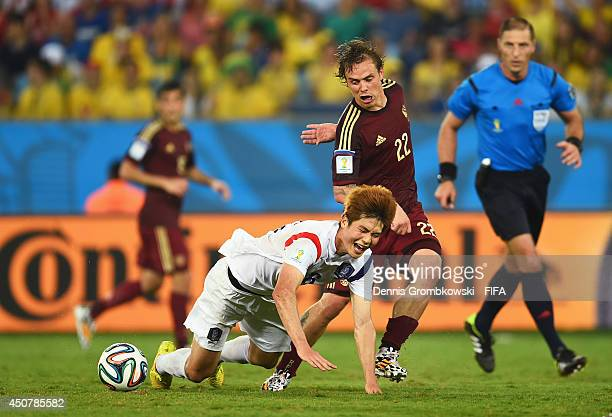 Ki SungYueng of South Korea is brought down by Andrey Yeshchenko of Russia during the 2014 FIFA World Cup Brazil Group H match between Russia and...
