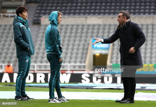 Ki SungYueng of Swansea City and Tom Carroll of Swansea City speak to the Carlos Carvalhal Manager of Swansea City on the pitch prior to the Premier...