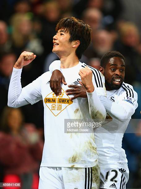 Ki SungYueng of Swansea City celebrates with Nathan Dyer as he scores their first goal during the Barclays Premier League match between Swansea City...
