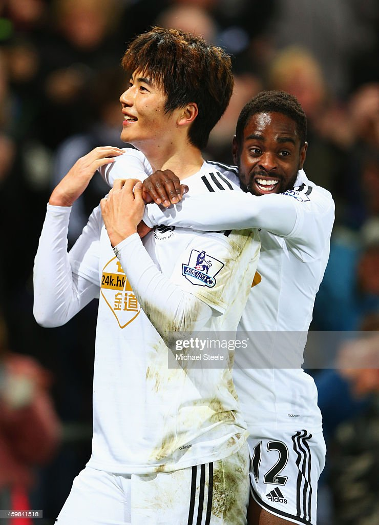 Ki Sung-Yueng of Swansea City celebrates with Nathan Dyer (R) as he scores their first goal during the Barclays Premier League match between Swansea City and Queens Park Rangers at Liberty Stadium on December 2, 2014 in Swansea, Wales.