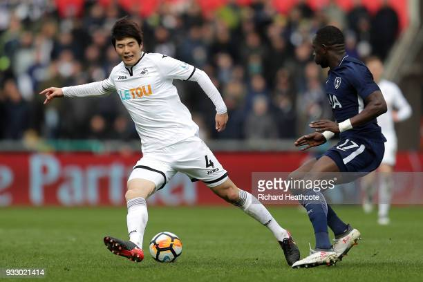 Ki SungYueng of Swansea City is challenged by Moussa Sissoko of Tottenham Hotspur during The Emirates FA Cup Quarter Final match between Swansea City...