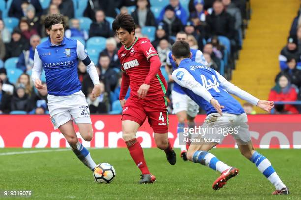 Ki SungYueng of Swansea City runs past Adam Reach and Frederico Venancio of Sheffield Wednesday during The Emirates FA Cup Fifth Round match between...
