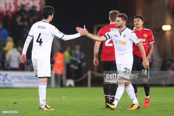 Ki Sungyueng of Swansea City shakes hands with Angel Rangel of Swansea City during dthe Carabao Cup Fourth Round match between Swansea City and...